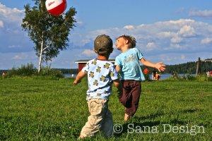 Pojat pelaamassa pallolla